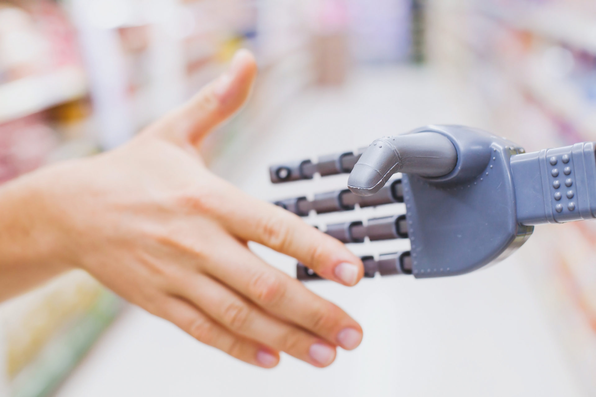 robot and human hands in handshake, high tech